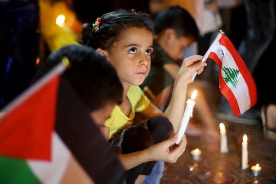 بين علمي لبنان وفلسطين أطفال يحملون الشموع تضامنًا مع ضحايا لبنان