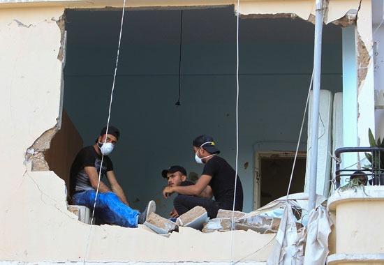 لبنانيون يجلسون في منزلهم الذي دمر بعد انفجار ميناء بيروت