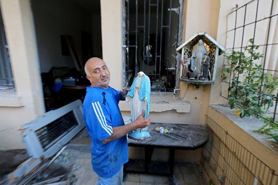 لبناني يحمل تمثال مريم العذراء الذي تضرر بعد انفجار بيروت