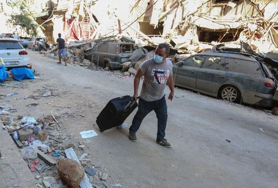 لبناني تاركًا منزله بعد تدميره إثر الانفجار