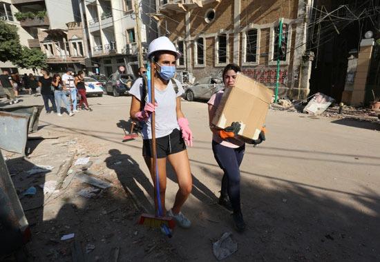 متطوعون ينظفون الشوارع بعد انفجار لبنان