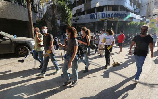 لبنانيون فى طريقهم لموقع الانفجار لازالة اثاره وتنظيف الشوارع