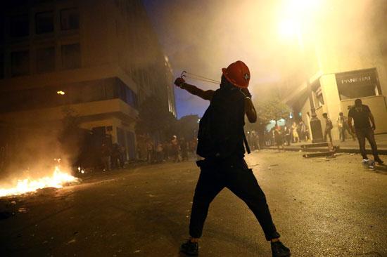 متظاهر يقذف الامن بالحجارة