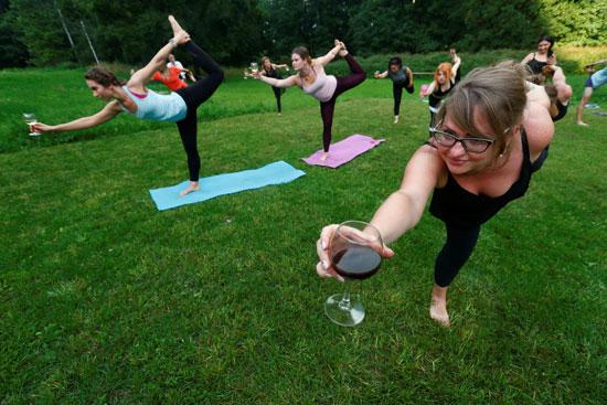 سيدة تحمل كأس النبيذ خلال ممارسة اليوجا