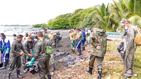 متطوعون يحاولون إزالة بقع النفط من المياه