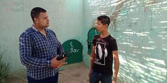 محرر اليوم السابع مع شقيق الضحية امام قبره