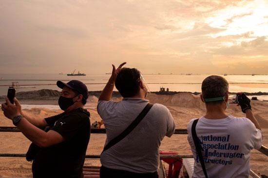 السكان المحليون يلتقطون صورًا من جسر للمشاة يطل على خليج مانيلا