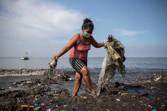 امرأة تلتقط القمامة على طول الساحل الملوث