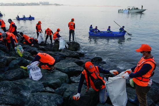 عمال ومتطوعون حكوميون يلتقطون القمامة على طول شاطئ خليج مانيلا