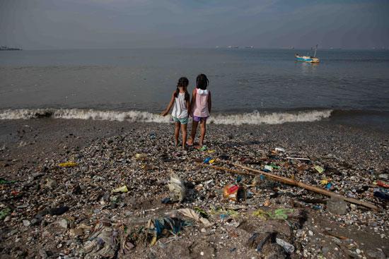 طفلتان ينظران إلى ساحل باسكو المليء بالقمامة في خليج مانيلا
