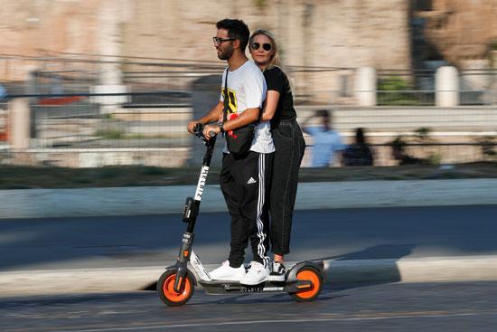 اثنان على دراجة بخارية كهربائية بالقرب من الكولوسيوم في روما