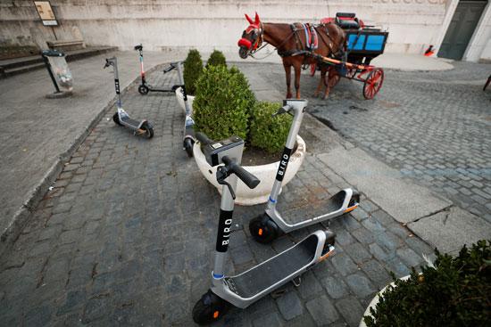 دراجات كهربائية وعربة بحصان قرب  نصب فيتوريانو التذكاري في ساحة فينيسيا