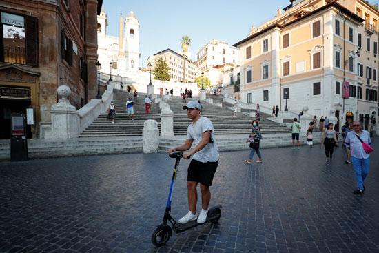 رجل يركب دراجة بخارية كهربائية أمام السلالم الإسبانية في روما