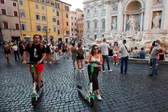 أشخاص يركبون دراجات بخارية كهربائية في نافورة تريفي