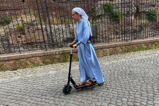 راهبة تركب دراجة بخارية كهربائية بالقرب من الكولوسيوم في روما