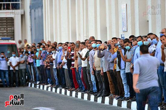 العمال ينتظرون وصول الجثمان