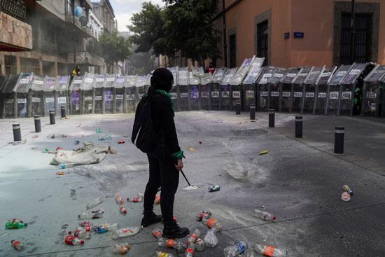 متظاهرة مكسيكية تقف أمام جحافل الشرطة