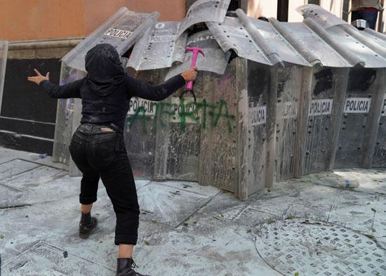 متظاهرة تحاول الهجوم على قوات الأمن