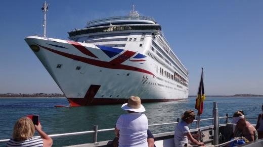 عدد من السائحين يلتقطون الصور لإحدى السفن الراسية