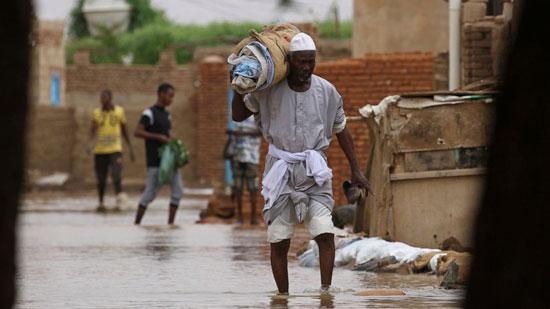 رجل يحمل أغراضه بعد الفيضان