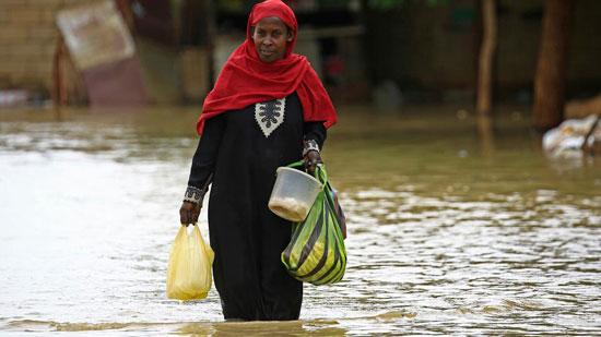 امراة سودانية تشتري الطعام رغم الفيضان