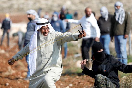 رجل فلسطيني يلقى الحجارة على جنود الاحتلال