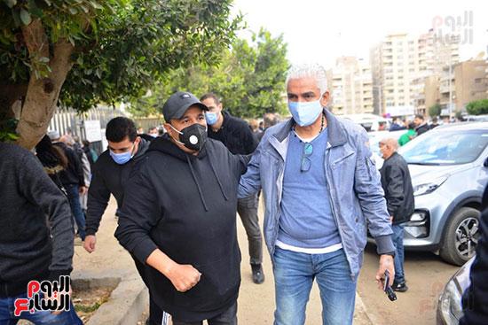 محمد فؤاد يرتدى كمامة فى جنازة زوج شقيقته