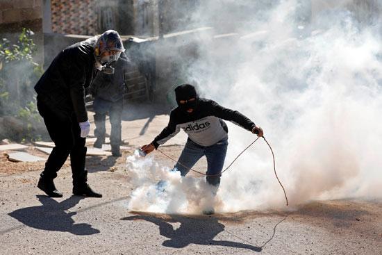 فلسطيني يمسك بقنبلة غاز