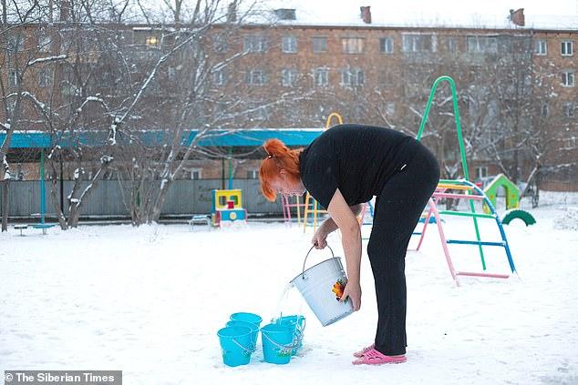 مدرس في مدرسة حكومية تملأ دلوًا من الماء البارد ليغمر الأطفال أنفسهم به في سيبيريا ، روسيا