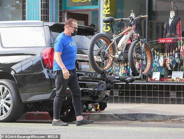 أرنولد شوارزنيجر  قرب سيارته ودراجته