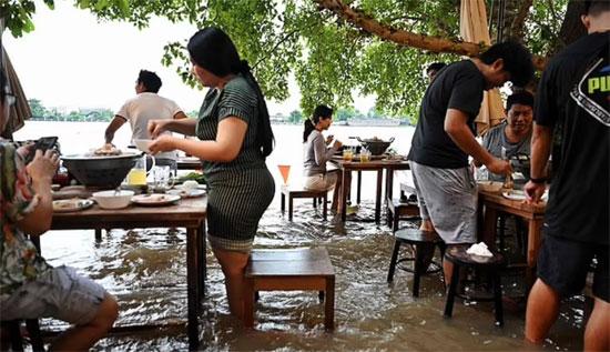 ظل مقهى Chaopraya Antique ، في Nonthaburi ، بالقرب من بانكوك ، مفتوحًا على البريد ويتدفق العملاء للاستمتاع بإثارة تجنب الأمواج الناتجة عن مرور القوارب