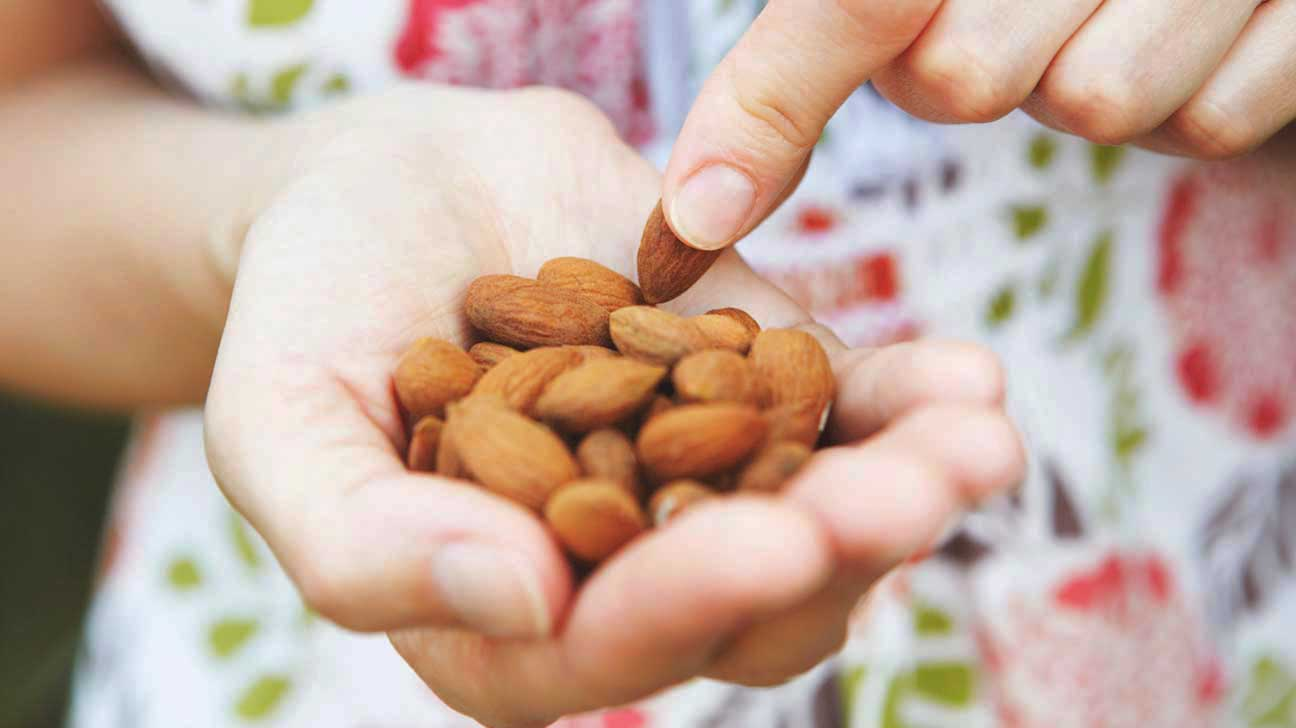 woman-holding-almonds-in-palm-of-hand-1296x728-1
