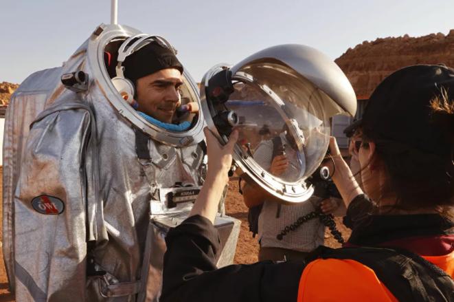 تقنيون يساعدون رواد الفضاءعلى ارتداء زي رائد فضاء، أثناء التدريب