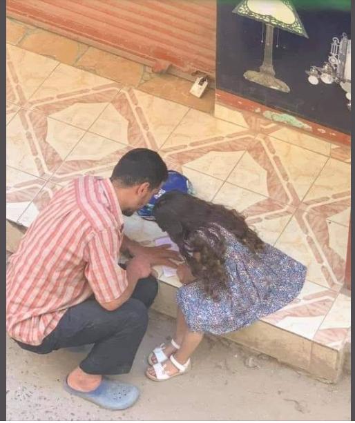 أب يجلس بجوار ابنته فى الشارع لتكملة واجبها المدرسى