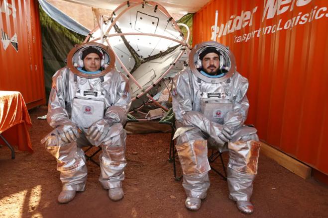 اثنان من رواد الفضاء يجلسان داخل ما يشبه قمرة المركبة الفضائية، أثناء التدريب
