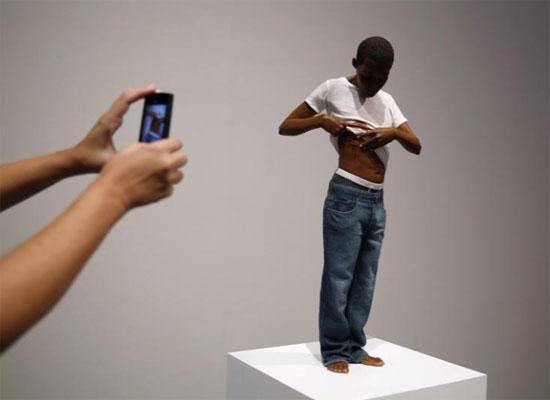 شخص يلتقط صورا لمنحوتة بعنوان الشباب للنحات الأسترالي رون مويك
