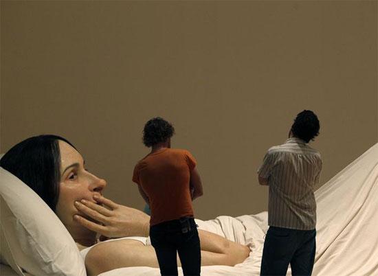 أفراد من الجمهور ينظرون إلى تمثال بعنوان في السرير لرون مويك