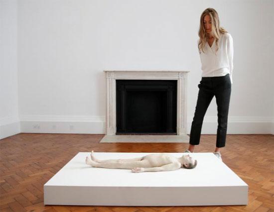 مساعد معرض يقف بجانب منحوتة بعنوان الأب الميت للفنان الأسترالي رون مويك