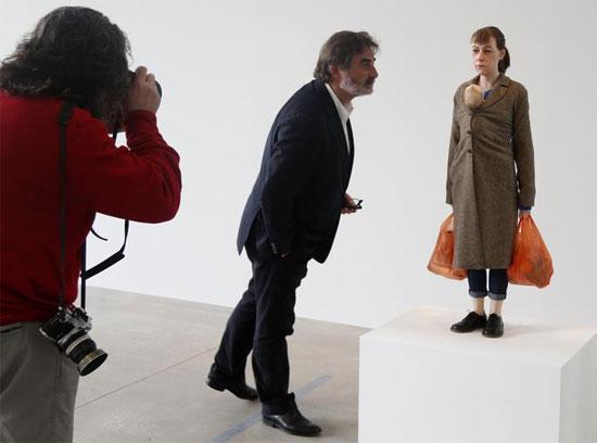 زائر ينظر إلى تمثال بعنوان المرأة مع التسوق ،  للفنان رون مويك