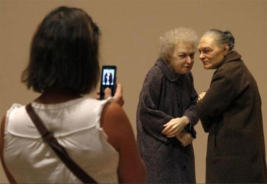 امرأة تلتقط صورة لمنحوتة بعنوان امرأتان لرون مويك