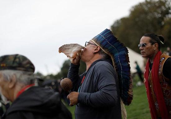 رجل ينفخ في بوق صدفة محارة أثناء الصلاة في احتفال شروق الشمس