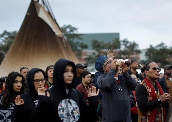 رجل ينفخ في بوق محارة أثناء الصلاة في احتفال شروق الشمس للسكان الأصليين في نيويورك