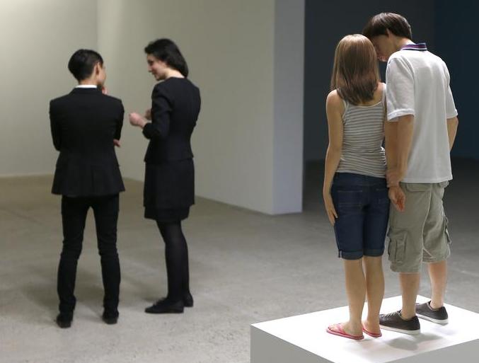 موظفون يقفون بجوار تمثال بعنوان زوجين شابين