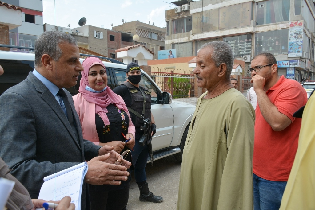 جبر الخواطر.. محافظ سوهاج يلتقط صورا تذكارية مع عمال النظافة فى الشارع