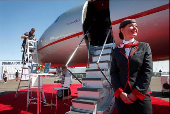 مضيفة الطيران تقف أمام طائرة أعمال من طراز VistaJet Global 7500