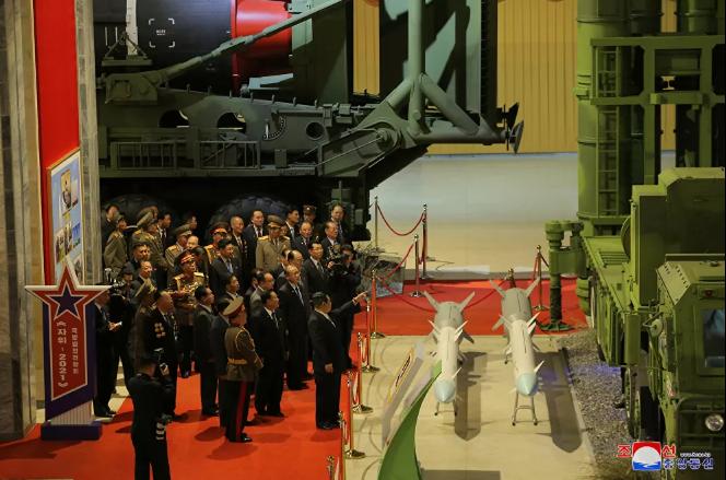 زعيم كوريا الشمالية كيم جونغ أون يتحدث إلى المسؤولين بجوار الأسلحة والمركبات العسكرية المعروضة (2)