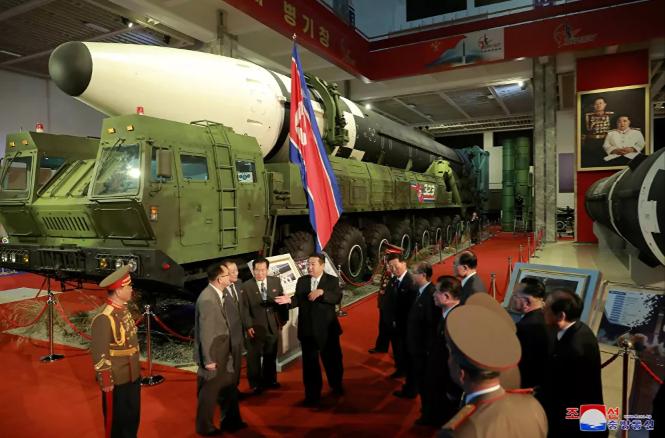 زعيم كوريا الشمالية كيم جونغ أون و المسؤولين بجوار الأسلحة والمركبات العسكرية ا