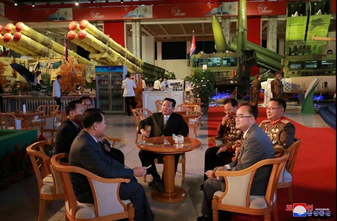 زعيم كوريا الشمالية كيم جونغ أون يتحدث إلى المسؤولين بجوار الأسلحة والمركبات العسكرية المعروضة