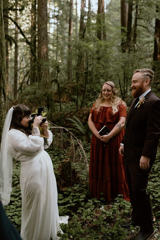 The bride takes a picture of her groom