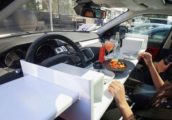 الناس يتناولون الغداء في سياراتهم خارج مطعم في مدينة الكويت